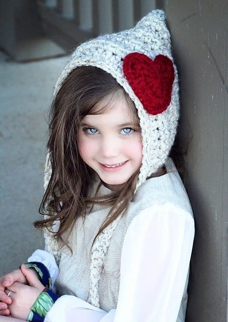 Nena con capucha de duende con un gran corazón rojo de adorno en ganchillo