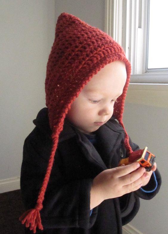 Bebé jugando y posando con un gorrito duende en ganchillo