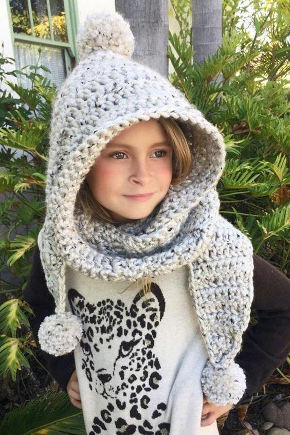 Nena con capucha y bufanda unidas, hecho en ganchillo en tono gris piedra y con pompones