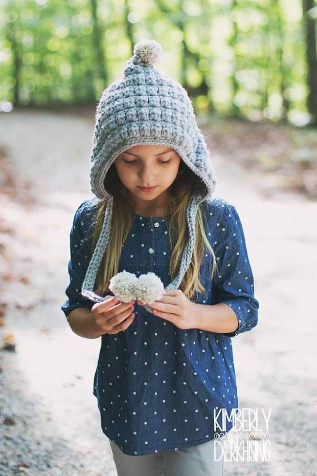 Foto de niña con un gorrito hecho en ganchillo jugando con los pompones